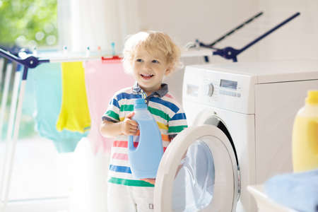 Child in a laundry room with washing machine or tumble dryer. Kid helping with family chores. Modern household devices and washing detergent in white sunny home. Clean washed clothes on drying rack. Stock Photo