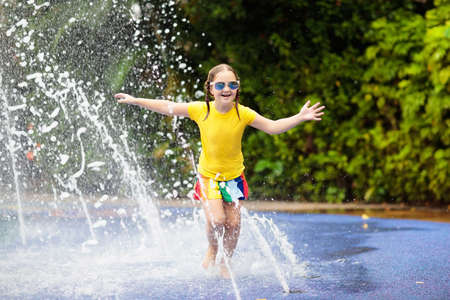 Kids play in aqua park. Children at water playground of tropical amusement park. Little girl at swimming pool. Child playing at water slide on summer vacation in Asia. Swim wear for young kid. Stock Photo - 108993800