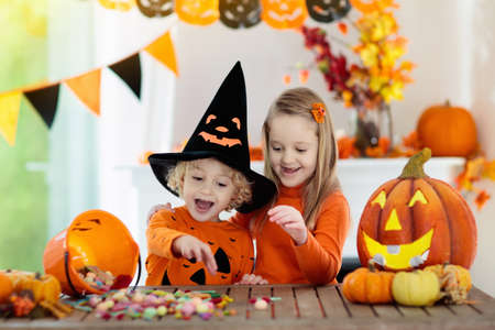 Little girl and boy in witch costume on Halloween trick or treat. Kids holding candy in pumpkin lantern bucket. Children celebrate Halloween at decorated fireplace. Family trick or treating. Banco de Imagens
