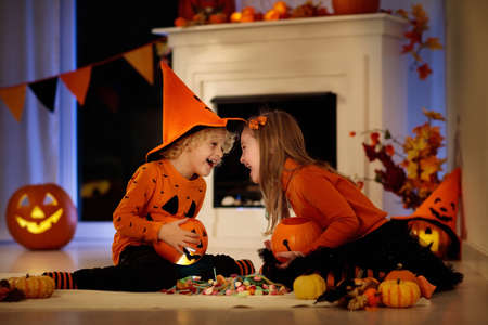 Little girl and boy in witch costume on Halloween trick or treat. Kids holding candy in pumpkin lantern bucket. Children celebrate Halloween at decorated fireplace. Family trick or treating. Stock Photo