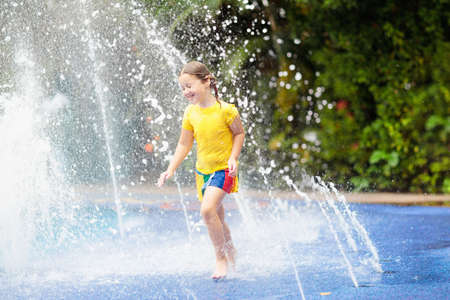 Kids play in aqua park. Children at water playground of tropical amusement park. Little girl at swimming pool. Child playing at water slide on summer vacation in Asia. Swim wear for young kid. Stock Photo - 108993927
