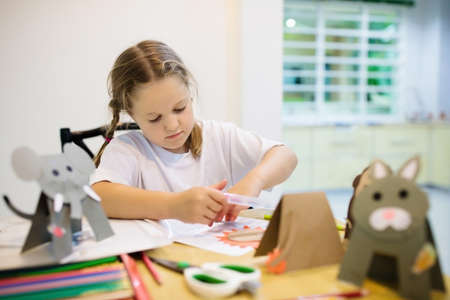 Crafts for kids. Child making colorful paper animals at art class. Creative little girl with glue stick and scissors creating do it yourself toys. Children crafting. School kid doing craft homework. Stockfoto