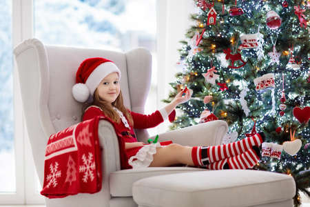 Child decorating Christmas tree and opening present and gift at home. Kid with Xmas gifts and toys. Little girl in Santa dress and hat at fireplace. Family with kids celebrate winter holidays.