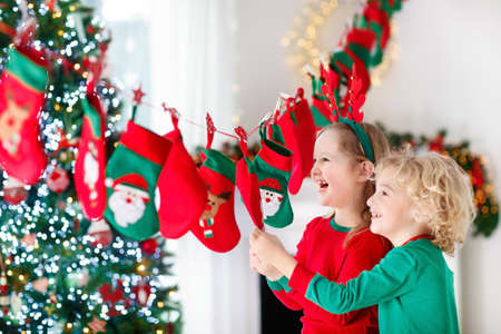 Kids opening Christmas presents. Child searching for candy and gifts in advent calendar on winter morning. Decorated Christmas tree for family with children. Little girl and boy in Xmas pajamas.