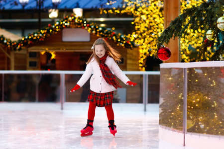 Kids ice skating in winter park rink. Children ice skate on Christmas fair. Little girl with skates on cold day. Snow outdoor fun for child. Winter sports. Xmas family vacation with kid.