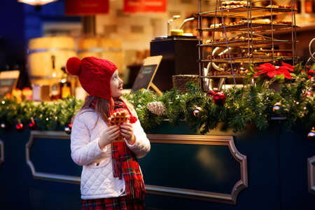 Children shopping on traditional Christmas market in Germany on snowy winter day. Kids buying waffle, candy, pastry and gingerbread in fair sweet shop. Little girl choosing sweets in Xmas bakery.
