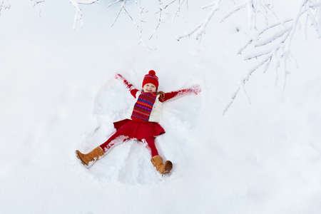 Child making snow angel on sunny winter morning. Kids winter outdoor fun. Family Christmas vacation. Little girl playing in snow after heavy storm. Active children outdoors on Xmas day. Stockfoto