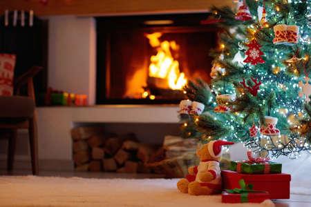 Weihnachtsbaum mit Geschenken am geschmückten Kamin. Familienfeier der Winterferien. Wohnzimmerinnenraum mit offenem Kamin und Weihnachtsbaum mit Geschenken für Kinder.