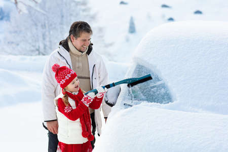 Father and child brushing and shoveling snow off car after storm. Parent and kid with winter brush and scraper clearing family car after overnight snow blizzard. Christmas vacation in the mountains.