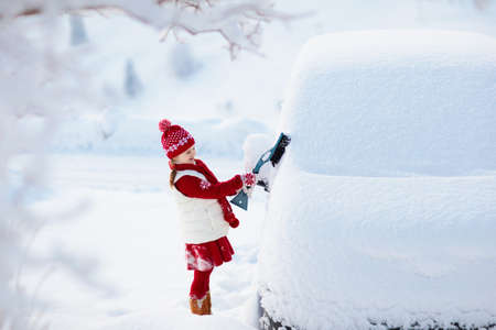Child brushing snow off car after storm. Kid with winter brush and scraper clearing family car after overnight snow blizzard. Family Christmas vacation in the mountains. Kids shoveling snow.