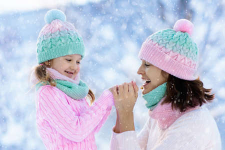 Mother and child in knitted winter hats play in snow on family Christmas vacation. Handmade wool hat and scarf for mom and kid. Knitting for kids. Knit outerwear. Woman and little girl in snowy park. Imagens