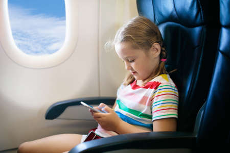 Child in airplane. Kid with mobile phone in air plane in window seat. Flight entertainment for kids. Traveling with young children. Kids fly and travel. Family vacation. Girl playing with smartphone.