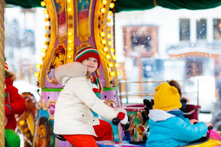 Kids at Christmas fair. Child at traditional street Xmas market in Germany. Winter outdoor fun. Little girl in knitted hat riding carousel horse in outdoor amusement park in winter holiday season.