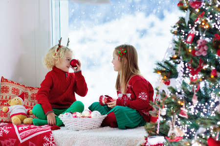 Child decorating Christmas tree at home. Little boy and girl in knitted sweater with handmade Xmas ornament. Family celebrating winter holidays. Kids decorate living room and window for Christmas.