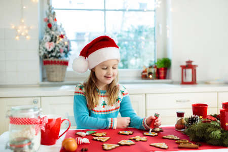 Kids bake Christmas cookies. Child in Santa hat cooking, decorating gingerbread man for Xmas celebration. Family preparing sweets in white kitchen with Christmas tree on snowy winter day. Stock Photo