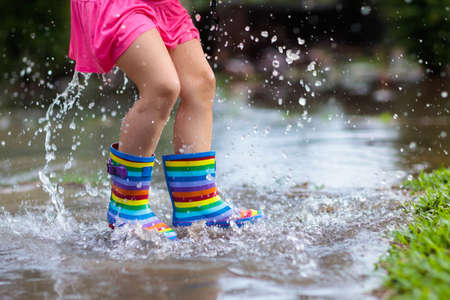 Kid playing out in the rain. Children with umbrella and rain boots play outdoors in heavy rain. Little girl jumping in muddy puddle. Kids fun by rainy autumn weather. Child running in tropical storm.
