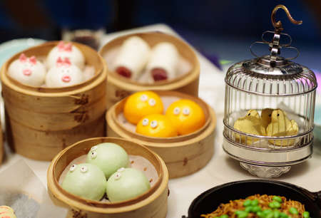 Dim sum, traditional Chinese dumpling in bamboo steamer, pig and animal theme for kids. Street food for children in China, Hong Kong. Family dinner with steamed dumplings. Banco de Imagens