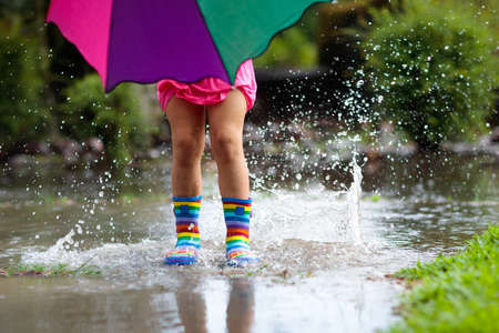 Kid playing out in the rain. Children with umbrella and rain boots play outdoors in heavy rain. Little girl jumping in muddy puddle. Kids fun by rainy autumn weather. Child running in tropical storm. Stok Fotoğraf - 112620056