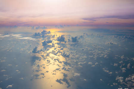 Ocean at sunset or sunrise, view from airplane window. Sea waves and clouds from above. Stock Photo