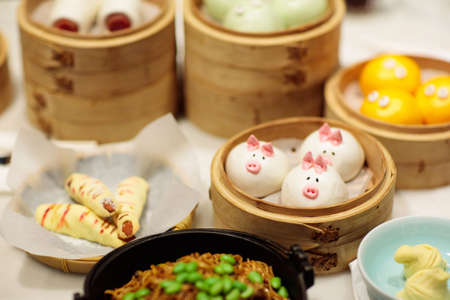 Dim sum, traditional Chinese dumpling in bamboo steamer, pig and animal theme for kids. Street food for children in China, Hong Kong. Family dinner with steamed dumplings. Stock Photo
