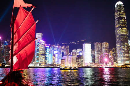 Hong Kong harbor view from traditional junk boat at night during famous laser show. Travel in China, Asia. Sailing on historical ship in Hong Kong Victoria harbor at symphony of light evening show.
