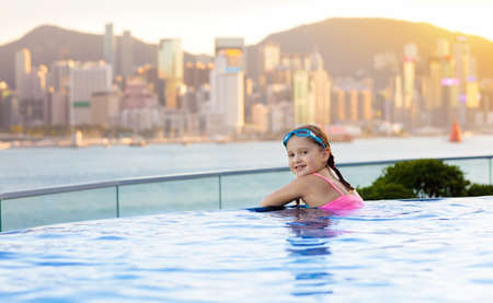 Children swimming in roof top outdoor pool on family vacation in Hong Kong. City skyline from infinity pool in luxury hotel in China. Kids swim and enjoy skyscraper view in Asia. Travel with child.