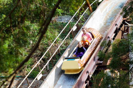 Family with kids on roller coaster in amusement theme park. Children riding high speed water slide attraction in entertainment fun fair during summer vacation.