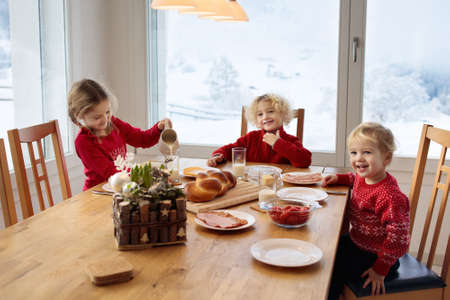 Kids having breakfast on Christmas morning. Family eating bread and drinking milk at home on snowy winter day. Children eat in sunny dining room at window with Swiss mountains and snow view. Stock Photo