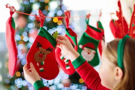 Kinder öffnen Weihnachtsgeschenke. Kind, das nach Süßigkeiten und Geschenken im Adventskalender am Wintermorgen sucht. Verzierter Weihnachtsbaum für Familie mit Kindern. Kleines Mädchen im Weihnachtspyjama. Standard-Bild