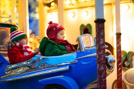 Kids at Christmas fair. Child at traditional street Xmas market in Germany. Winter outdoor fun. Girl in winter knitted hat Stock Photo