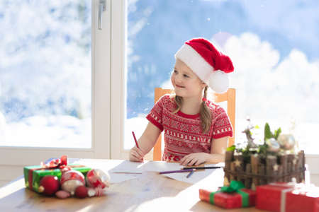 Child writing letter to Santa on Christmas eve. Kids write Xmas present wish list. Little girl sitting in decorated living room with big window on sunny winter day in the mountains, snow outside. Stock Photo