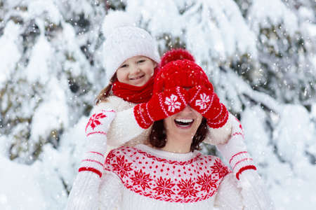 Mother and child in knitted winter hats play in snow on family Christmas vacation. Handmade wool hat and scarf for mom and kid. Knitting for kids. Knit outerwear. Woman and little girl in snowy park. 写真素材