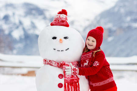 Child building snowman. Kids build snow man. Boy and girl playing outdoors on snowy winter day. Outdoor family fun on Christmas vacation in the mountains. Children play in Swiss mountain landscape. 版權商用圖片