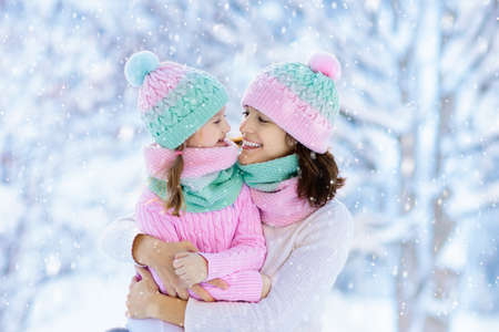 Mother and child in knitted winter hats play in snow on family Christmas vacation. Handmade wool hat and scarf for mom and kid. Knitting for kids. Knit outerwear. Woman and little girl in snowy park.