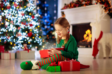 Child opening present at Christmas tree at home. Kid in elf costume with Xmas gifts and toys. Little girl with gift box and candy at fireplace. Family celebrating winter holidays. Home decoration.