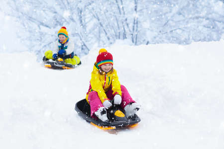 Little girl enjoying a sleigh ride. Child sledding. Toddler kid riding a sledge. Children play outdoors in snow. Kids sled in the Alps mountains in winter. Outdoor fun for family Christmas vacation. 版權商用圖片