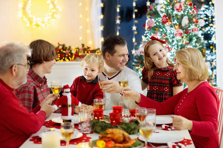 Family with children eating Christmas dinner at fireplace and decorated Xmas tree. Parents, grandparents and kids at festive meal. Winter holidays celebration and food. Kids open presents and gifts.