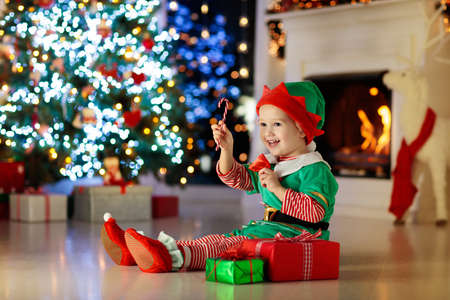 Child opening present at Christmas tree at home. Kid in elf costume with Xmas gifts and toys. Little baby boy with gift box and candy at fireplace. Family celebrating winter holidays. Home decoration.