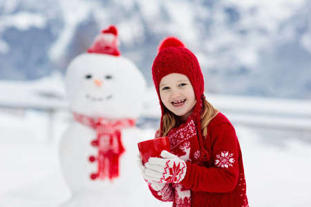 Child building snowman. Kids build snow man. Boy and girl playing outdoors on snowy winter day. Outdoor family fun on Christmas vacation in the mountains. Children play in Swiss mountain landscape. Banque d'images