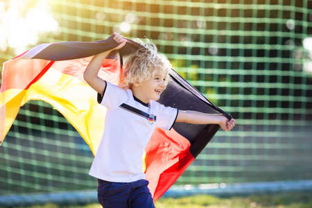 Kids play football on outdoor field. Germany team fans with national flag. Children score a goal at soccer game. Child in German jersey and cleats kicking ball. Fan celebrating victory at pitch.