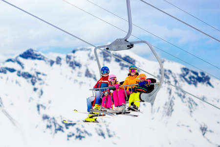 Family in ski lift in Swiss Alps mountains. Skiing with young kids. Christmas vacation. Winter outdoor sports for active family.