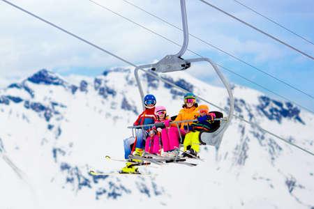 Familie in skilift in de bergen van de Zwitserse Alpen. Skiën met jonge kinderen. Kerst vakantie. Winter buitensporten voor actieve familie. Stockfoto