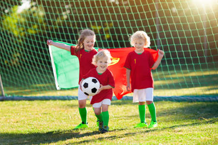Kids play football on outdoor field. Portugal team fans with national flag. Children score a goal at soccer game. Child in Portuguese jersey and cleats kicking ball. Fan celebrating victory at pitch.