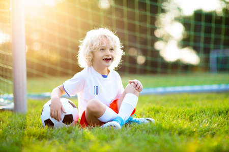 Kids play football on outdoor field. England team fans. Children score a goal at soccer game. Little boy in English jersey and cleats kicking ball. Football pitch. Sports training for player. Stockfoto - 112620686