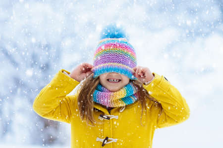 Child in knitted hat playing in snow on Christmas vacation. Winter outdoor fun. Knitting and outerwear for family. Kids play in snowy park. Little girl in knit scarf and mittens catching snowflakes.