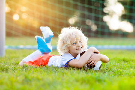 Kids play football on outdoor field. England team fans. Children score a goal at soccer game. Little boy in English jersey and cleats kicking ball. Football pitch. Sports training for player. Stockfoto - 112620710