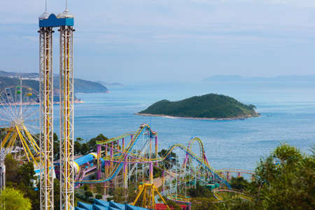 Ocean theme park in Hong Kong. Roller coaster and entertainment attraction at sea side in amusement theme park in Hong Kong. View from mountain top.