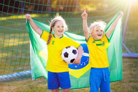 Kids play football on outdoor field. Brazil team fans with national flag. Children score a goal at soccer game. Child in Brazilian jersey and cleats kicking ball. Fan celebrating victory at pitch. Stockfoto - 112620788