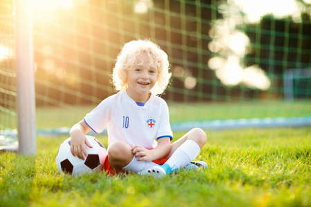 Kids play football on outdoor field. England team fans. Children score a goal at soccer game. Little boy in English jersey and cleats kicking ball. Football pitch. Sports training for player.