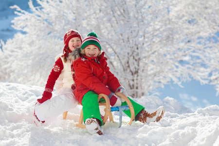 Kleines Mädchen und Junge genießen Schlittenfahrt. Kinderrodeln. Kleinkind reitet einen Schlitten. Kinder spielen draußen im Schnee. Kinderschlitten im verschneiten Park im Winter. Spaß im Freien für Familienweihnachtsferien.